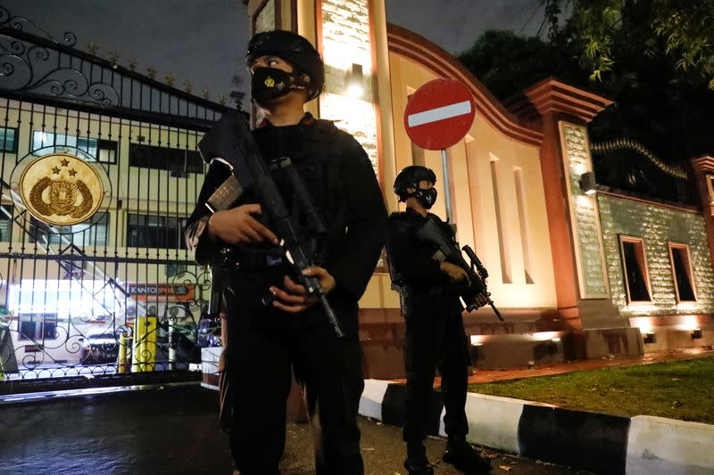 Armed police officers stand guard at the gate of national police headquarters, in Jakarta