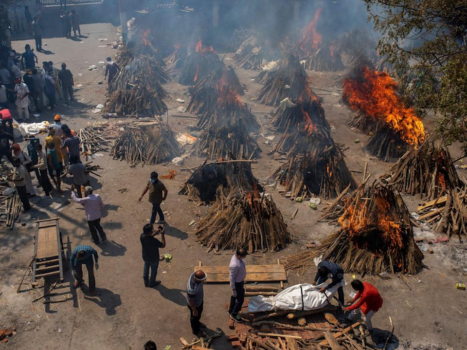 <p>File: In this 24 April photo, multiple funeral pyres of victims of Covid-19 burn at a ground that has been converted into a crematorium in Delhi</p> (AP)
