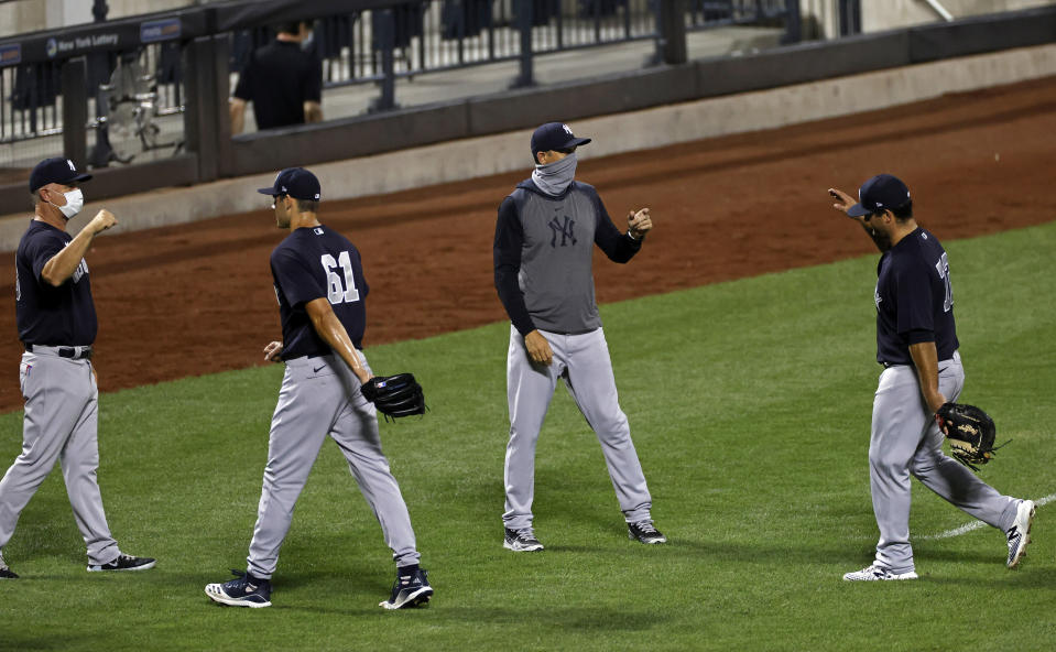 New York Yankees manager Aaron Boone celebrates with his players after defeating the New York Mets in a baseball spring training game Saturday, July 18, 2020, in New York. The Yankees won 9-3. (AP Photo/Adam Hunger)