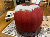 <p>Carefully start applying the mixture to the top of the pumpkin. This is easiest with a plastic spoon or knife. The more you put on the top the more it will drip down for a creepy effect. Just be careful to not get the mixture inside the black eyes and nose you traced earlier.</p>