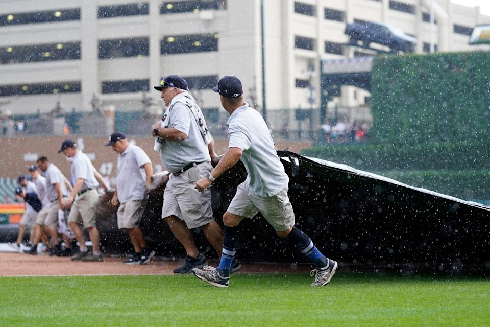 The Comerica Park grounds crew roll out the tarp during the fifth inning of a baseball game between the Detroit Tigers and the Toronto Blue Jays, Sunday, Aug. 29, 2021, in Detroit.