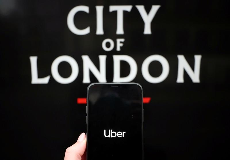 The Uber logo is displayed on a mobile phone in this picture illustration