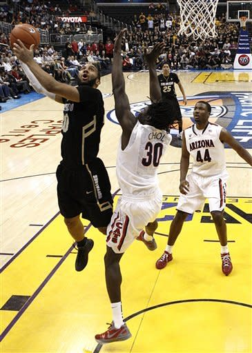 Colorado's Carlon Brown, left, drives to the basket as he is defended by Arizona's Angelo Chol, center, during the first half of an NCAA college basketball game in the finals of the Pac-12 conference championship in Los Angeles, Saturday, March 10, 2012. (AP Photo/Jae C. Hong)