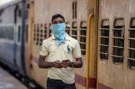 A passenger wearing a facemask amid concerns over the spread of the COVID-19 novel coronavirus waits on a platform to board a train at a railway station in Secunderabad, the twin city of Hyderabad, on March 20, 2020. (Photo by NOAH SEELAM / AFP) (Photo by NOAH SEELAM/AFP via Getty Images)
