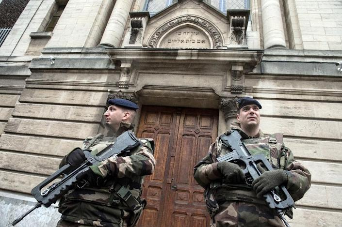 French soldiers stand guard in front of the entrance of a synagogue in Lille, northern France, on January 13, 2015 following attacks that left 17 people dead, beginning at the office of satirical magazine Charlie Hebdo (AFP Photo/Philippe Huguen)