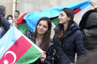 Azerbaijanis with the national flags celebrate after the country's President claimed Azerbaijani forces have taken Shushi, a key city in the Nagorno-Karabakh region that has been under the control of ethnic Armenians for decades in Baku, Azerbaijan, Sunday, Nov. 8, 2020. (AP Photo)