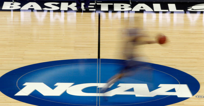 FILE - In this March 14, 2012, file photo, a player runs across the NCAA logo during practice at the NCAA tournament college basketball in Pittsburgh. California will let college athletes hire agents and make money from endorsements, defying the NCAA and setting up a likely legal challenge that could reshape U.S. amateur sports. (AP Photo/Keith Srakocic, File)