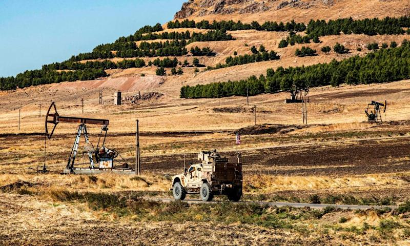 A US military armoured vehicle drives in a patrol past a an oil well in Rumaylan in Syria's northeastern Hasakeh province.