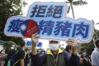 """A participant shows a slogan """"Anti-ractopamine pork"""" during a protest in Taipei, Taiwan, Sunday, Nov. 22. 2020. Thousands of people marched in streets on Sunday demanding the reversal of a decision to allow U.S. pork imports into Taiwan, alleging food safety issues. (AP Photo/Chiang Ying-ying)"""