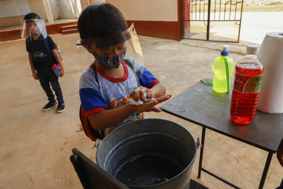 Wearing a mask and face shield to curb the spread of the new coronavirus, a student washes his hands before entering for his first day of class at the Valentin Gomez Farias Indigenous Primary School in Montebello, Hecelchakan, Campeche state, Monday, April 19, 2021. Campeche is the first state to transition back to the classroom after a year of remote learning due to the pandemic. (AP Photo/Martin Zetina)