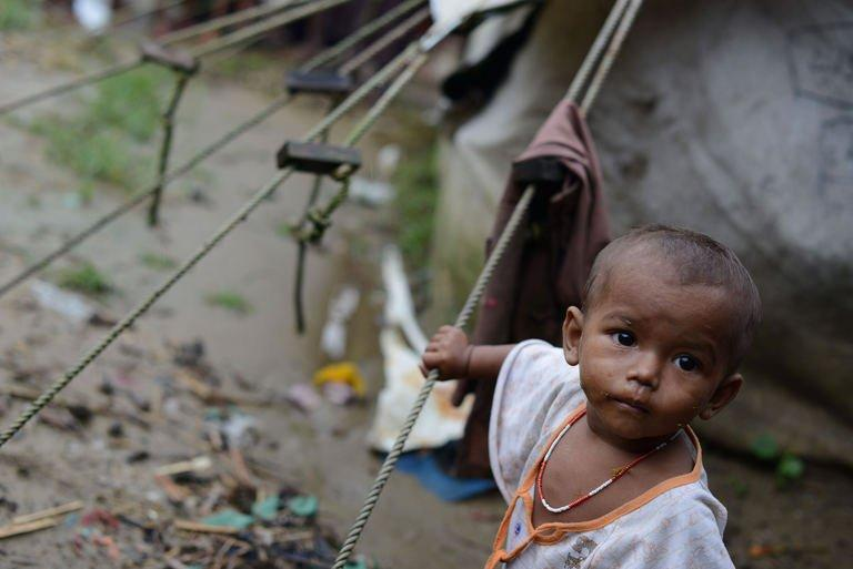 """A Muslim Rohingya child stands outside his tent at the Say Thamagyi Internally Displaced Persons (IDP) camp, located on the outskirts of Sittwe in October 2012. The United Nations' humanitarian chief Valerie Amos said almost half a million people are displaced """"in need of assistance"""" in Myanmar"""
