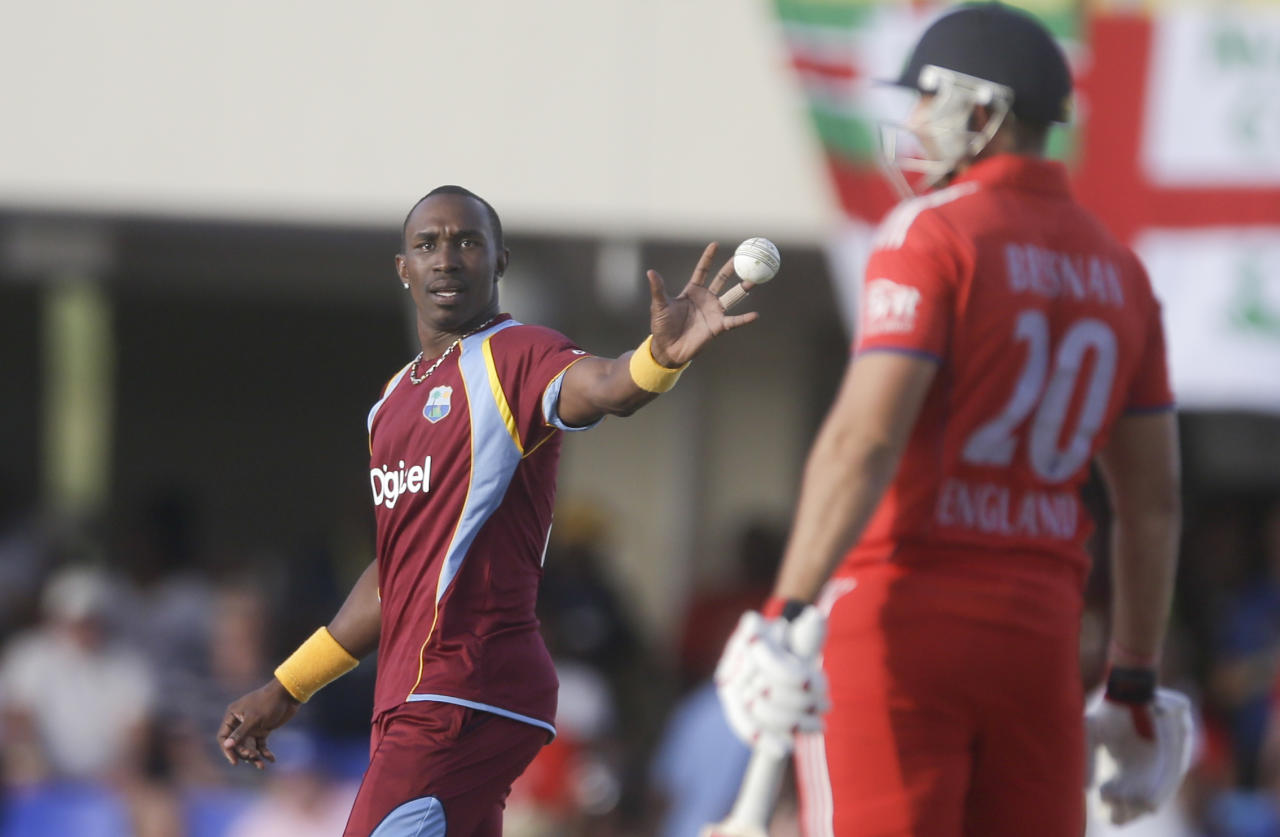 West Indies' captain Dwayne Bravo receives the ball during a one-day international cricket match against England at the Sir Vivian Richards Cricket Ground in St. John's, Antigua, Friday, Feb. 28, 2014. At right England's Tim Bresnan. (AP Photo/Ricardo Mazalan)