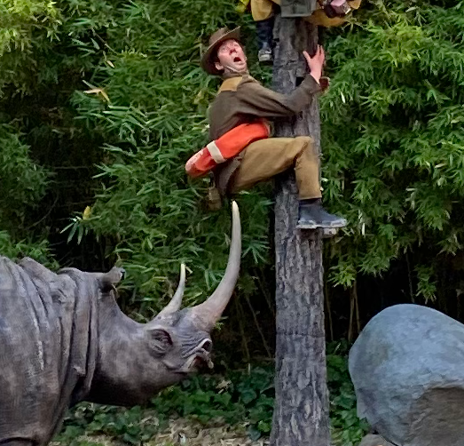 A man with a life vest around his waist, about to get poked by a rhino
