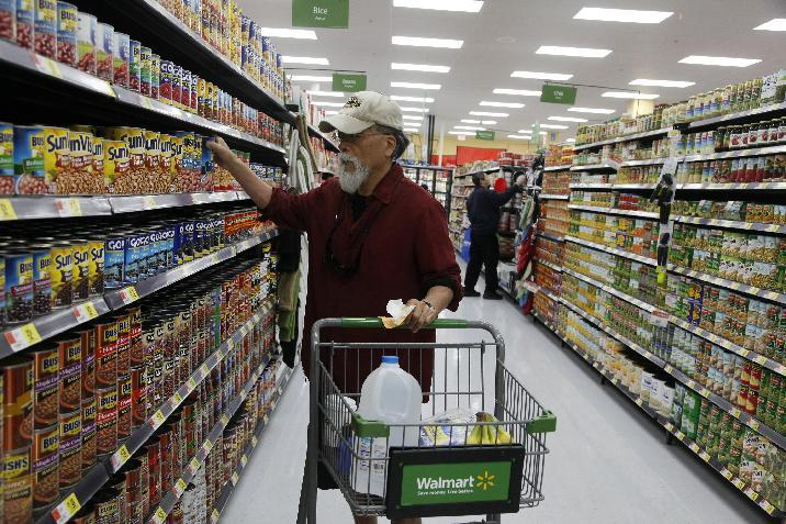 In this Thursday, Sept. 19, 2013, photo, costumers shop at the new Walmart Neighborhood Market in Los Angeles. The government reports how much consumers spent and earned in September on Friday, Nov. 8, 2013. (AP Photo/Nick Ut)