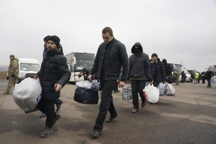 Ukrainian war prisoners walk after being released after a prisoner exchange, near Odradivka, eastern Ukraine, Sunday, Dec. 29, 2019. Ukrainian forces and Russia-backed rebels in eastern Ukraine have begun exchanging prisoners in a move aimed at ending their five-year-long war. The move is part of an agreement brokered earlier this month at a summit of the leaders of Ukraine, Russia, Germany and France. (AP Photo/Evgeniy Maloletka)