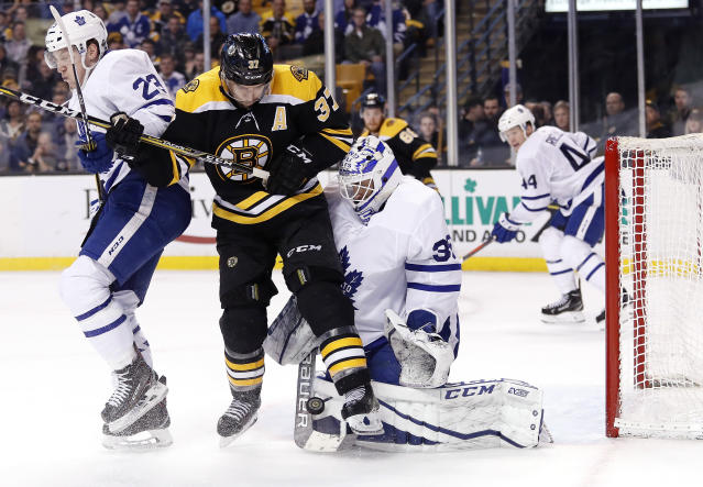 Toronto Maple Leafs goaltender Curtis McElhinney makes a save as Boston Bruins' Patrice Bergeron and defenseman Travis Dermott battle for position during the second period of Game 2 of an NHL hockey first-round playoff series in Boston, Saturday, April 14, 2018. (AP Photo/Winslow Townson)