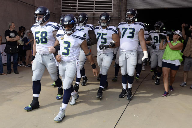 <p>Seattle Seahawks quarterback Russell Wilson (3) and center Justin Britt (68) walk to the field with arms linked after the national anthem had been played before an NFL football game between the Seahawks and the Tennessee Titans Sunday, Sept. 24, 2017, in Nashville, Tenn. Neither team was present on the field for the playing of the anthem. (AP Photo/Mark Zaleski) </p>