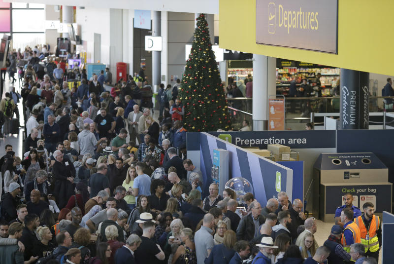 People wait near the departures gate at Gatwick airport, near London, as the airport remains closed with incoming flights delayed or diverted to other airports, after drones were spotted over the airfield last night and this morning, Thursday, Dec. 20, 2018. London's Gatwick Airport remained shut during the busy holiday period Thursday while police and airport officials investigate reports that drones were flying in the area of the airfield. (AP Photo/Tim Ireland)