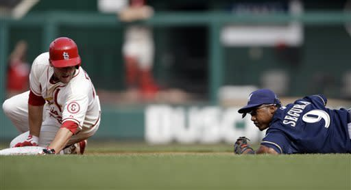 St. Louis Cardinals' David Freese, left, heads to second for a double as Milwaukee Brewers shortstop Jean Segura looks on during the third inning of a baseball game, Saturday, April 13, 2013, in St. Louis. (AP Photo/Jeff Roberson)