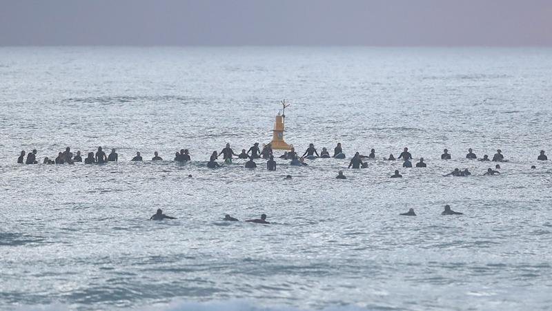 Surfers, pictured here paddling out in memory of Alex 'Chumpy' Pullin at Palm Beach.