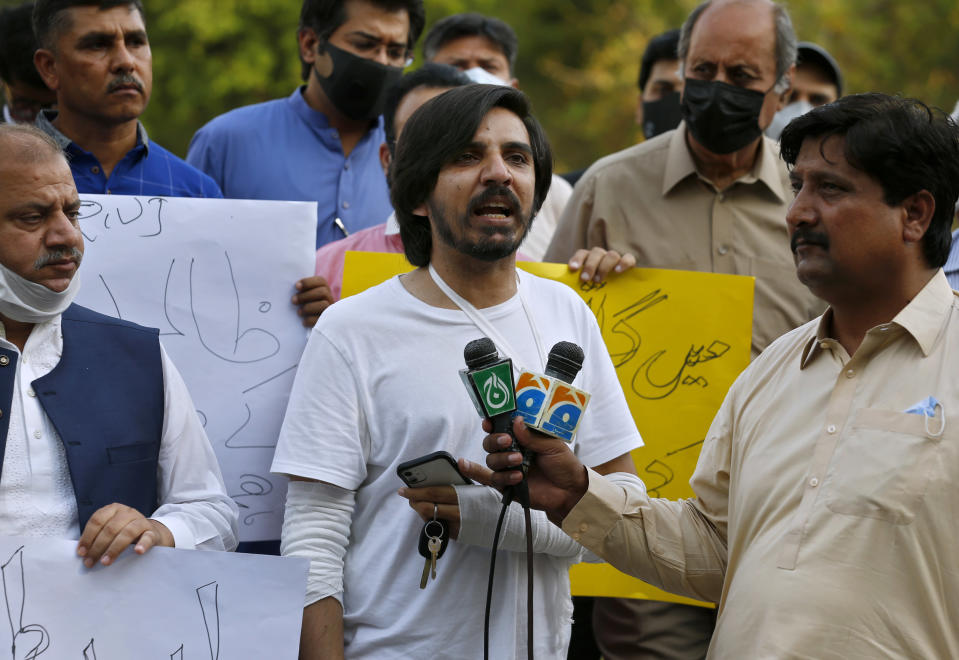 Pakistani journalist Asad Ali Toor, center, who was beaten and injured by three unidentified men in an attack, speaks during a demonstration called by journalists union to condemn the attack on journalists, in Islamabad, Pakistan, Friday, May 28, 2021. (AP Photo/Anjum Naveed)