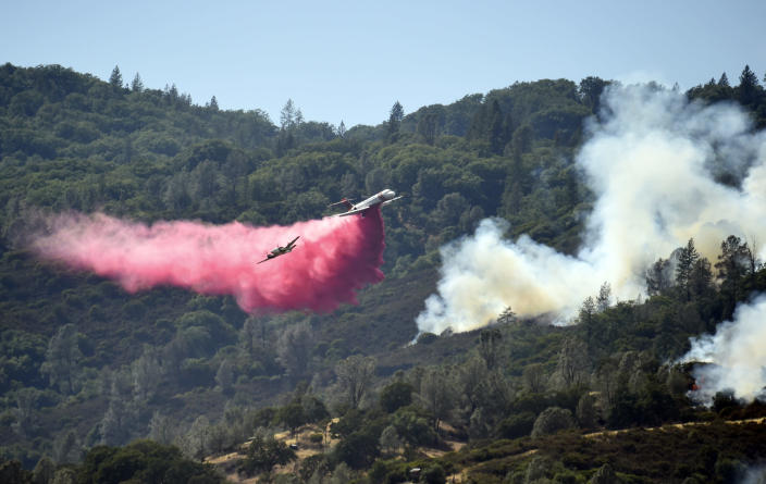 A spotter plane banks in front of an air tanker as it drops fire retardant on a burning hillside during the Ranch Fire in Clearlake Oaks, Calif., on Sunday, Aug. 5, 2018. (AP Photo/Josh Edelson)