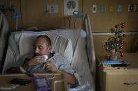 COVID-19 patient Francisco Ramirez wipes his face in his bed next to a small Christmas tree dropped off my his mother at Providence Holy Cross Medical Center in the Mission Hills section of Los Angeles, Tuesday, Dec. 22, 2020. (AP Photo/Jae C. Hong)