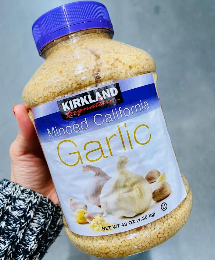 Hand holding a large container of minced garlic from costco