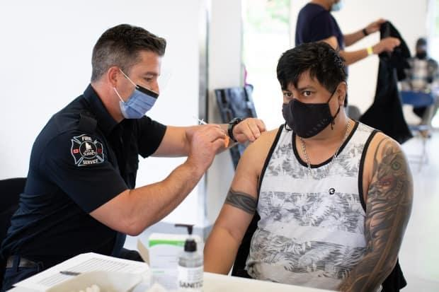 Surrey firefighter Shaun Hawley administers Pfizer vaccine during a vaccine clinic at Bear Creek Park in Surrey, B.C., on Monday, May 17, 2021.  (Maggie MacPherson/CBC - image credit)