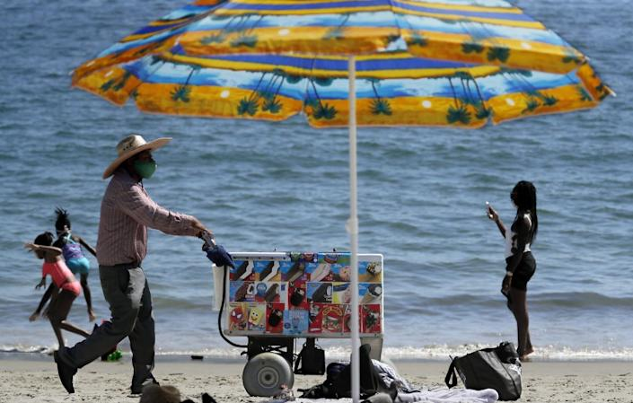 """An ice cream vendors pushes a cart along the sand at Junipero Beach in Long Beach on a warm afternoon. <span class=""""copyright"""">(Luis Sinco / Los Angeles Times)</span>"""
