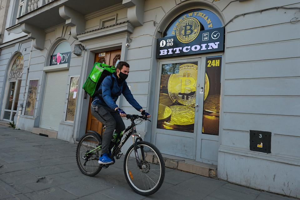 A Uber Eats currier wearing a protective mask passes in front of a Bitcoin exchange shop in Krakow's city center. On Saturday, April 18, 2020, in Krakow, Poland. (Photo by Artur Widak/NurPhoto via Getty Images)