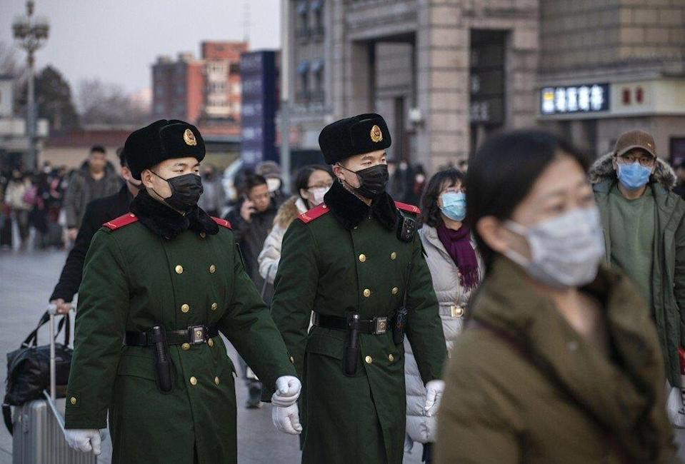 Chinese police officers patrol at Beijing Station before the annual Spring Festival. Officials and volunteers implement virus control members rigorously when an outbreak of coronavirus occurs. Photo: Getty Images