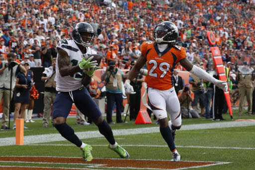 FILE - In this Sunday, Sept. 9, 2018, file photo, Seattle Seahawks wide receiver Brandon Marshall, left, hauls in a touchdown pass in the end zone as Denver Broncos defensive back Bradley Roby (29) looks on during the second half of an NFL football game in Denver. Marshalls debut with his sixth team went well in Week 1, even though Seattle ended up losing 27-24 to the Broncos. The 34-year-old had three receptions for 46 yards and a touchdown in his Seattle debut. (AP Photo/David Zalubowski, File)
