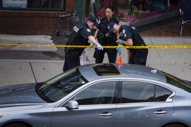 <p>Police investigate a car with a bullet hole within the scene of a shooting in east Toronto, on July 23, 2018. Police were trying Monday to determine what prompted a 29-year-old man to go on a shooting rampage in a popular Toronto neighborhood. (Photo: Christopher Katsarov/The Canadian Press via AP) </p>