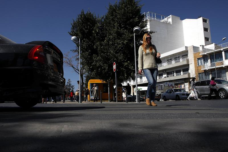 """A woman crosses a road in the old city of capital Nicosia, Cyprus, Wednesday, March 13, 2013. Cyprus' president Nicos Anastasiades says talks with international creditors for a much-needed rescue loan to keep the country from going bankrupt are paying off. Anastasiades urged patience, saying that it will soon become clear that """"hard work produces good results."""" (AP Photo/Petros Karadjias)"""
