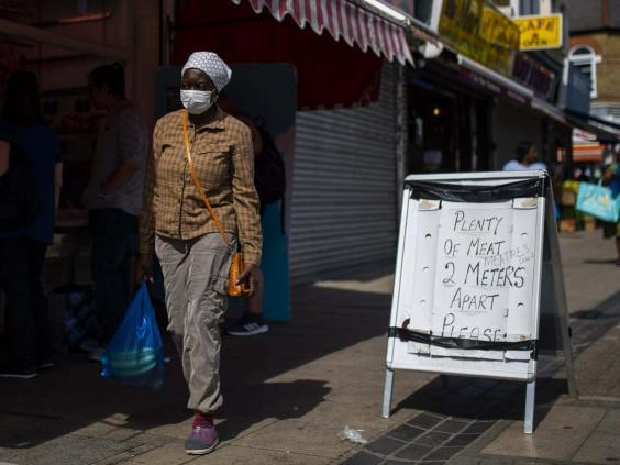 A woman walks past a social distancing sign outside a butchers in Walthamstow, London (Getty)