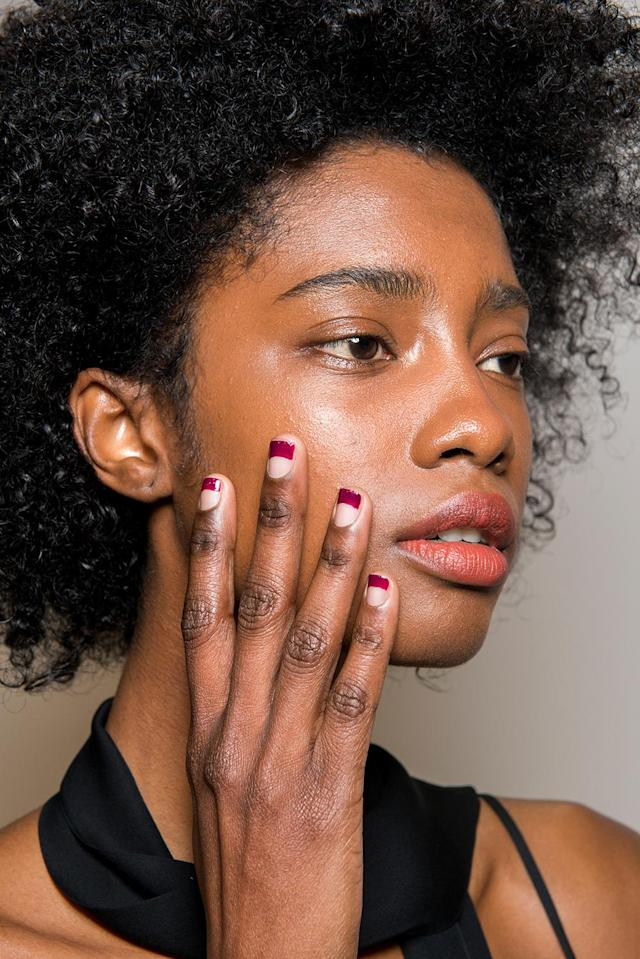 <p>Julie Kandalec for Essie created a dramatic crescent French manicure to play off the '70s feel of the collection. Three shades were used: Go Overboard, Bahama Mama, and Smokin' Hot. (Photo: Imaxtree) </p>