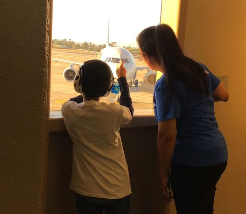 Michael and an American Airlines employee look out at the plane on the tarmac. (Photo Courtesy of Annette Martinez)