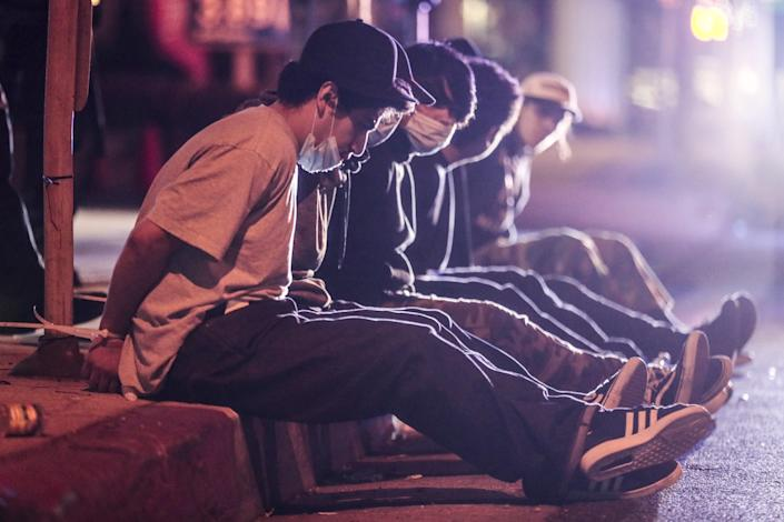 "Suspected looters sit handcuffed on Santa Monica Blvd. after being spotted running from a CVS store nearby. <span class=""copyright"">(Robert Gauthier/Los Angeles Times)</span>"