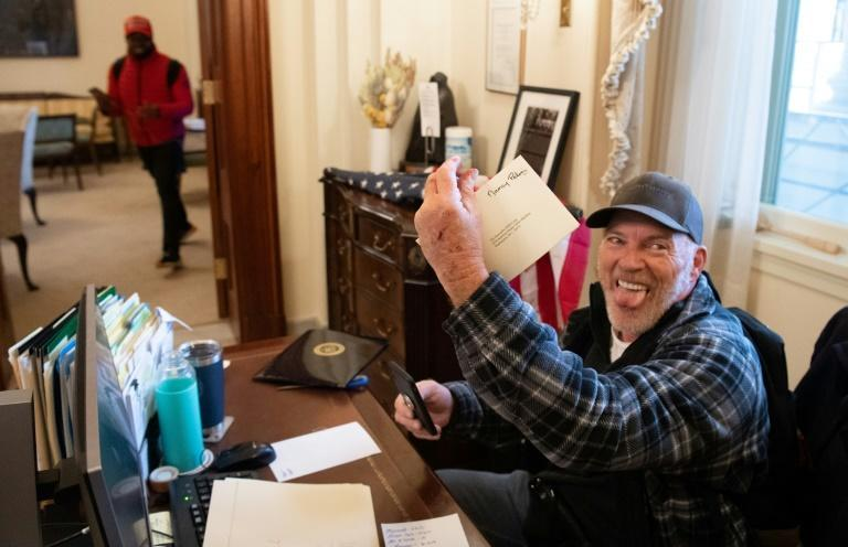 Richard Barnett, a supporter of US President Donald Trump, holds a piece of mail as he sits inside the office of House Speaker Nancy Pelosi after protestors breached the US Capitol
