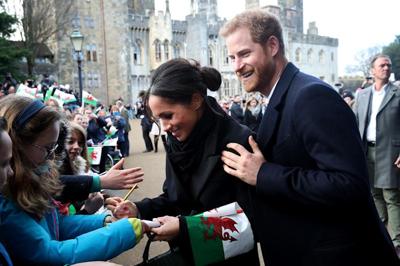 CARDIFF, WALES - JANUARY 18: Prince Harry and his fiancee Meghan Markle sign autographs and shake hands with children as they arrive to a walkabout at Cardiff Castle on January 18, 2018 in Cardiff, Wales. (Photo by Chris Jackson/Chris Jackson/Getty Images)
