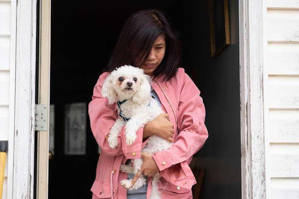 Fatima Quintana picks up her dog after attending school at Spartanburg High School Monday, March 2, 2020.