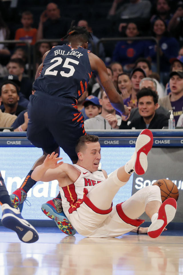 Miami Heat's Duncan Robinson, bottom, and New York Knicks' Reggie Bullock (25) dive after a loose ball during the second half of the NBA basketball game, Sunday, Jan. 12, 2020, in New York. The Knicks defeated the Heat 124-121. (AP Photo/Seth Wenig)