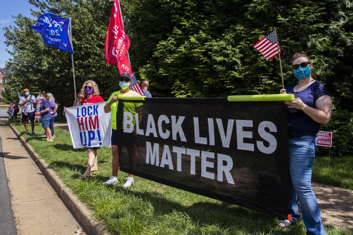 Supporters of President Donald Trump and protesters hold banners as they wait for the motorcade of President Trump outside the Trump National Golf Club in Sterling, Va., Sunday, Aug. 30, 2020. (AP Photo/Manuel Balce Ceneta)