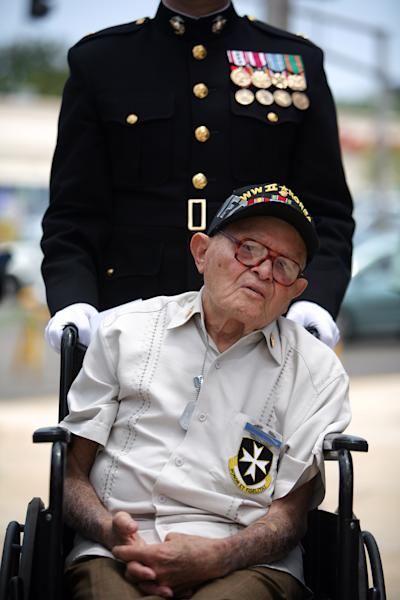 Korean War veteran Luis Ramos, 90, is pushed in a wheelchair by a Marine at a ceremony attended by more than a dozen surviving members of the famed 65th Infantry Regiment, in San Juan, Puerto Rico, Friday, Sept. 7, 2012. Ramos was decorated with a Bronze Star on Friday, nearly 60 years after leaving the service. The veteran served with the mostly Puerto Rican unit that fought in some of the bloodiest battles of the war. (AP Photo/Ricardo Arduengo)
