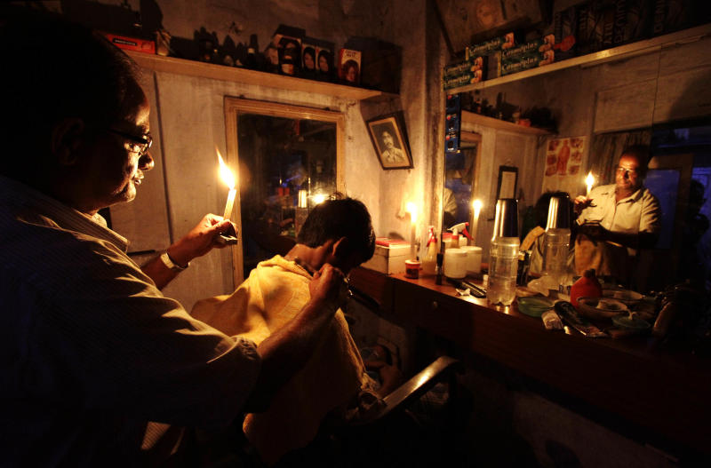 An Indian barber holding a candle,  has a haircut for a customer at his shop in Kolkata, India, Tuesday, July 31, 2012. India's energy crisis cascaded over half the country Tuesday when three of its regional grids collapsed, leaving 620 million people without government-supplied electricity for several hours in, by far, the world's biggest blackout. (AP Photo/Bikas Das)