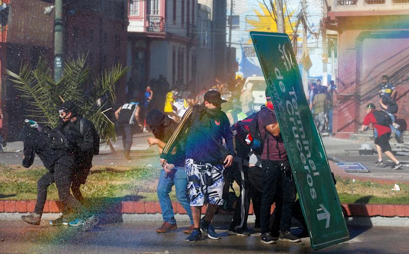 Demonstrators take cover with a traffic signal as they clash with security forces during a protest against Chile's government in Valparaiso, Chile on Oct. 28, 2019. (Photo: Rodrigo Garrido/Reuters)