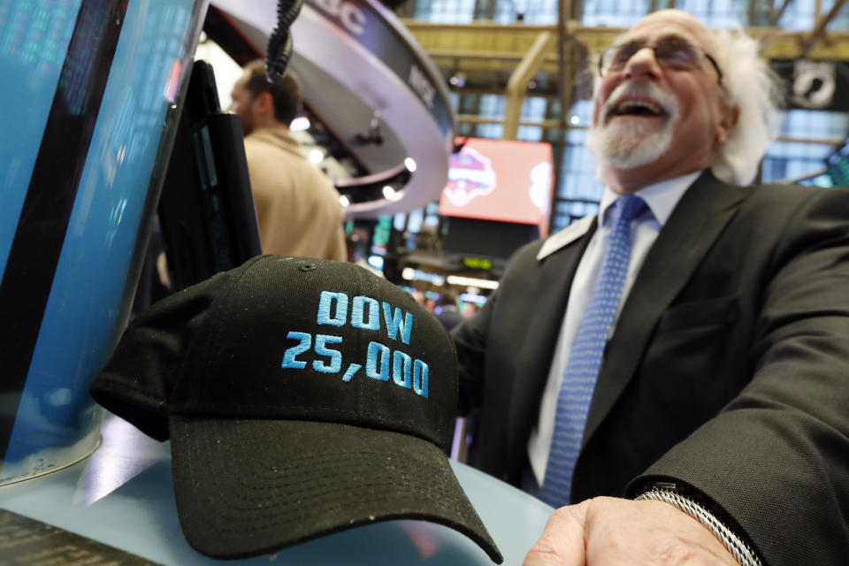 "FILE- In this Jan. 30, 2019, file photo trader Peter Tuchman smiles as he poses with an old ""Dow 25,000"" hat on the New York Stock Exchange trading floor. The bull market in stocks started with the U.S. still reeling from the Great Recession in March 2009. The bull turns 10 this weekend, having survived threats such as a debt crisis in Europe (2011), a slowdown in the Chinese economy (2015-2016), and fears of inflation and rising interest rates in the U.S. (AP Photo/Richard Drew, File)"