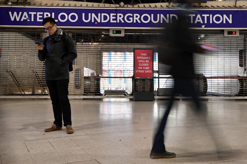 A man looks at his mobile phone at a barriered entrance to a tube station in Waterloo station