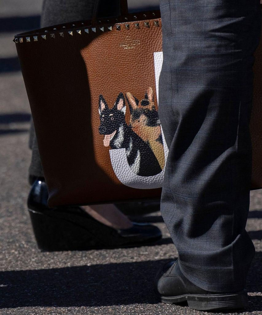 A member of the staff holds US First Lady Jill Biden's personal bag with a picture of the presidential pets, German Shepherds named Champ and Major, as she prepare to board a plane in Colorado Springs, Colorado, May 6, 2021. (Photo by CARLOS BARRIA / POOL / AFP) (Photo by CARLOS BARRIA/POOL/AFP via Getty Images)